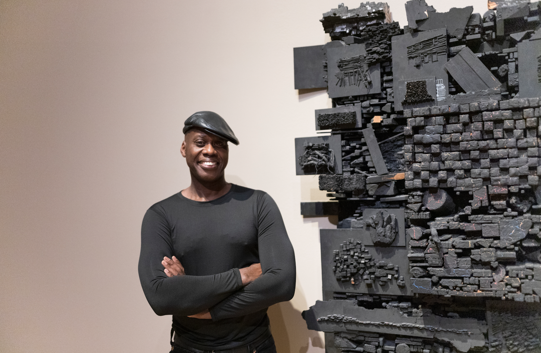Photograph of artist Leonardo Drew next to his sculpture made of black wood pieces