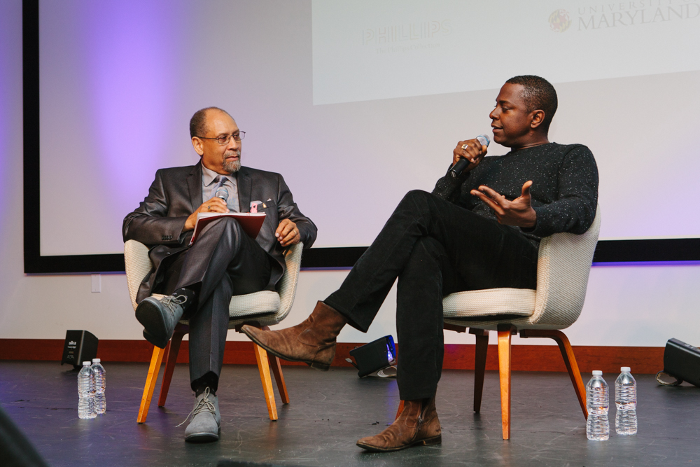 Artist Sanford Biggers and UMD professor Curlee Holton seated on a stage during an event, with Sanford holding a microphone