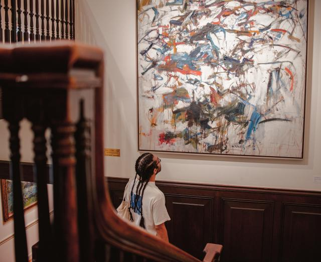 Visitor looking at Joan Mitchell painting in House Stairwell