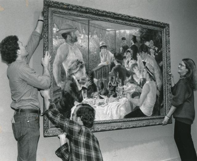 Black and white photograph of three people hanging up Renoir's Luncheon of the Boating Party