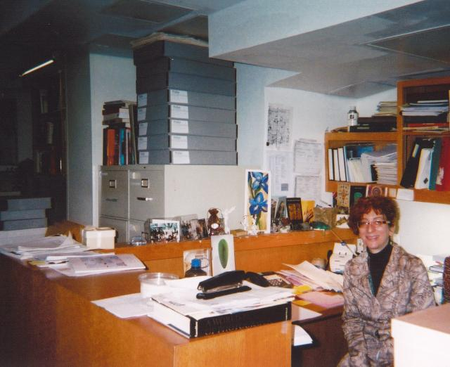 Photograph of a woman at a desk with a lot of papers and boxes