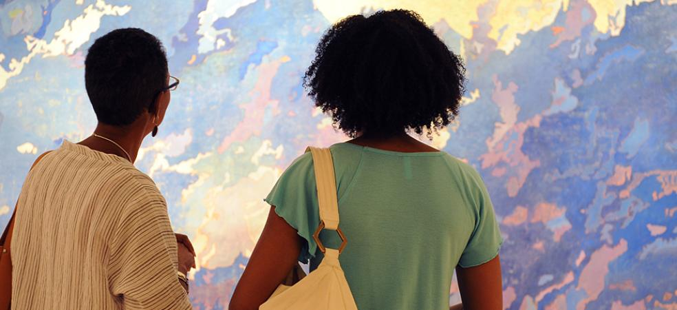 Visitors look at a painting