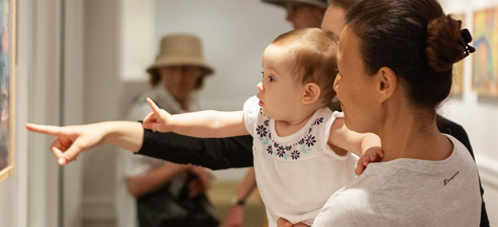 Photograph of woman holding a baby that is pointing at art