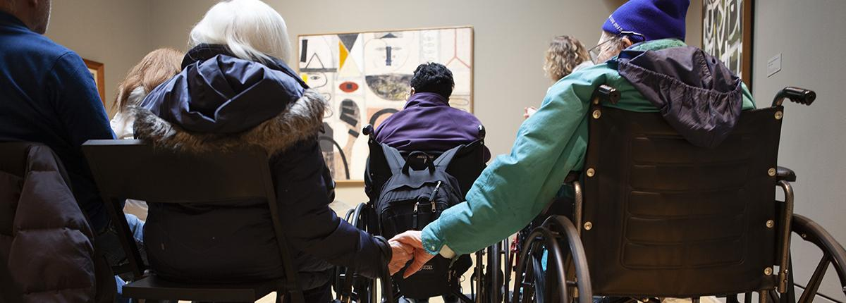 Photograph of two older adults--one in a wheelchair--sitting in a gallery looking at art and holding hands