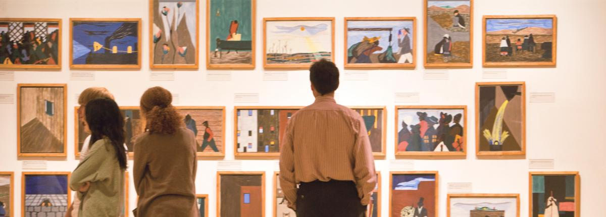 People looking at Jacob Lawrence's Migration Series