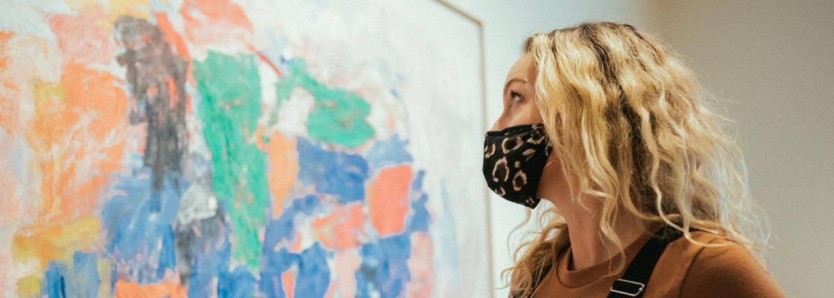 Visitor with mask on looking at painting by Philip Guston