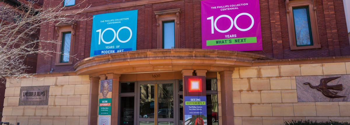 "Photo of the main entrance of The Phillips Collection with blue and pink banners with ""100"" on them"