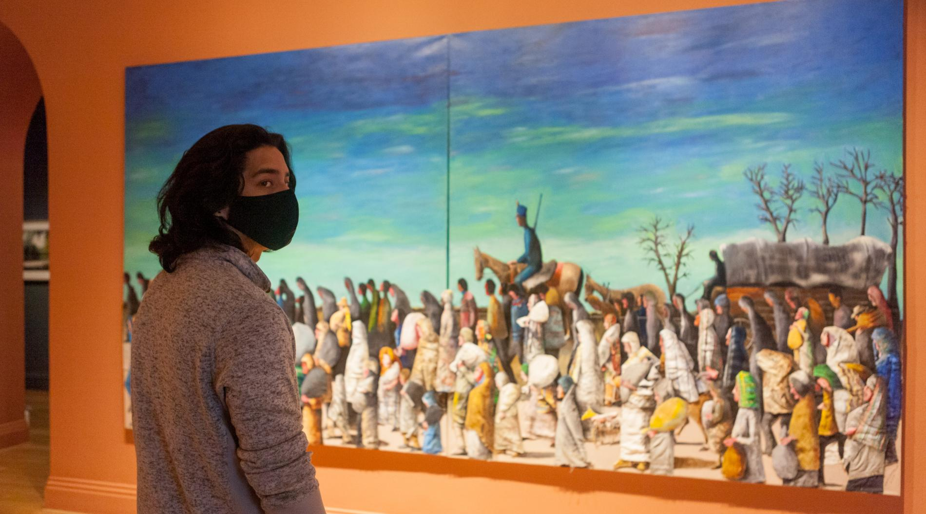 "Photo of a person standing in front of Benny Andrews's painting ""Trail of Tears"" and looking to the right"