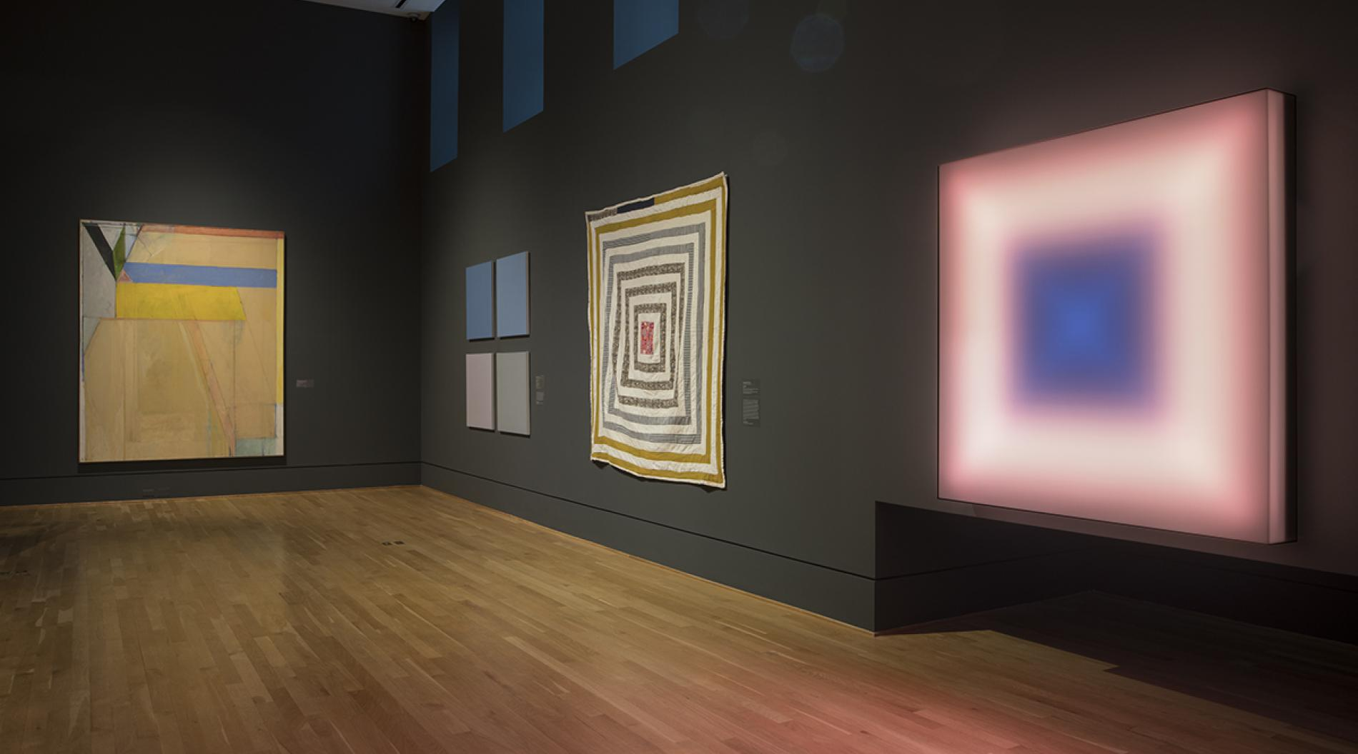 Photograph of four colorful artworks in a museum gallery with dark blue walls