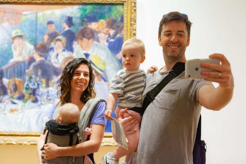 Photograph of family with two children taking a group selfie in front of Renoir's Luncheon of the Boating Party