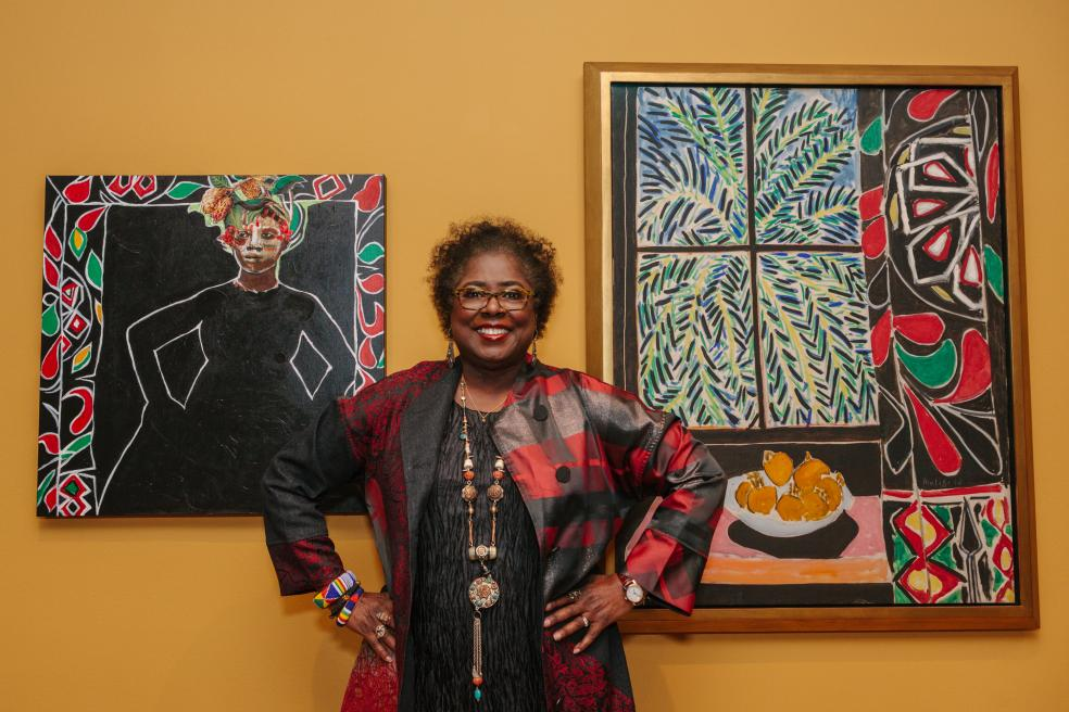 Photograph of a person standing between two paintings, hands on hips and smiling