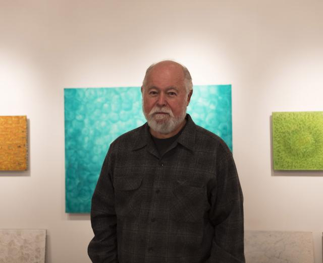 Photograph of Robin Rose with his artwork on the walls behind him