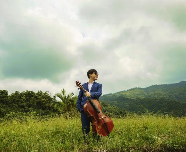 Man in field with cello