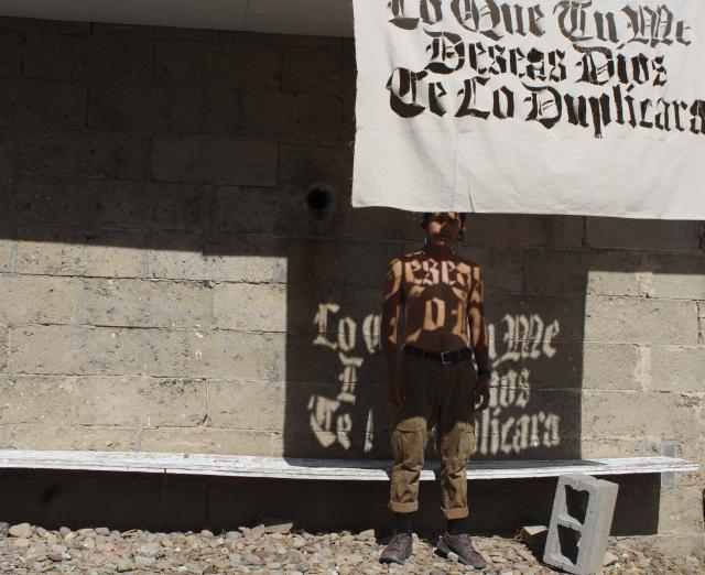 Photograph of Jonathan Herrera Soto standing in front of a building, shirtless, with a cloth with words cut out of it hanging in front of him