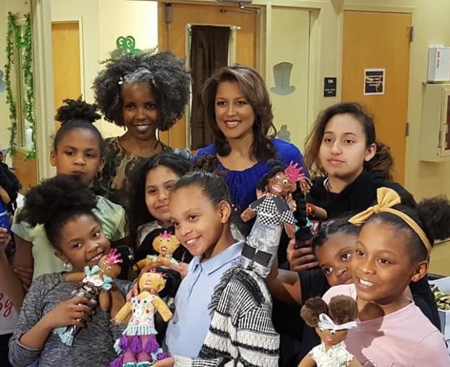 Photo of group of African American girls smiling and holding black dolls