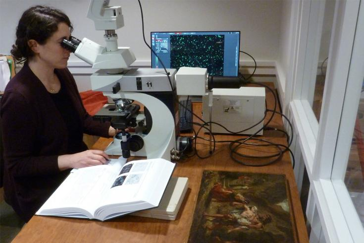 A conservationist looks through a microscope