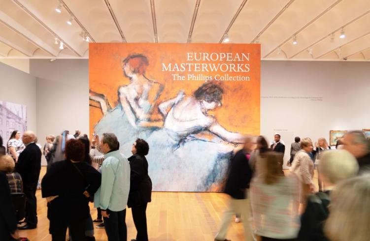 Photograph of a gallery with a lot of people mingling and a very large reproduction of Degas's Dancers at the Barre painting