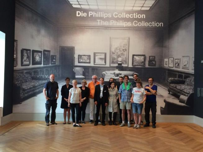 Photograph of a group of people in a big room, posing in front of a wall with a reproduction of an archival photograph of The Phillips Collection
