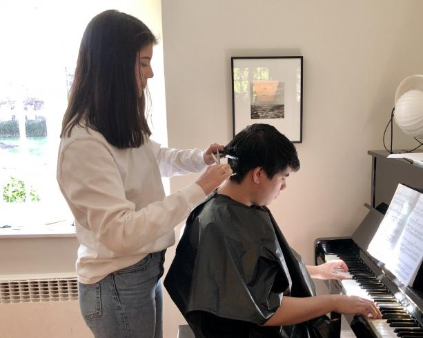 Photo of someone cutting the hair of someone that is playing the piano