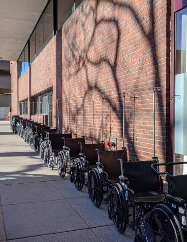 Photograph of a row of wheelchairs against a brick building