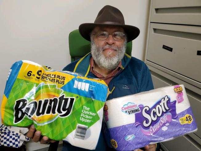 Photograph of man holding packages of toilet paper and paper towels