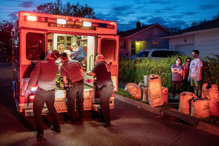 Photograph of EMS volunteers helping someone into an ambulance in front of a house