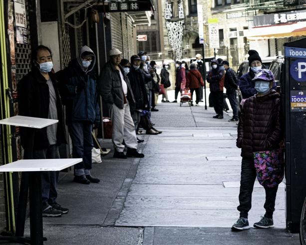 Photograph of people lined up outside on a sidewalk, with masks on