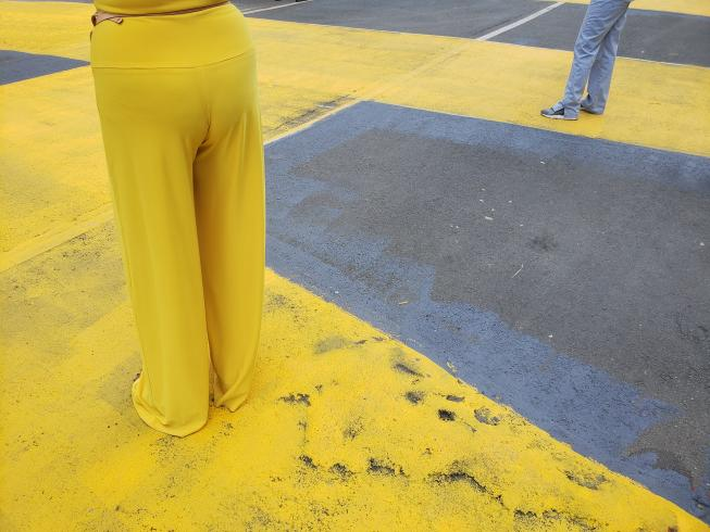 Photograph of someone wearing yellow pants standing on a street painted yellow