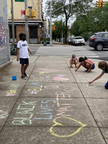Photograph of four people writing in chalk on the sidewalk
