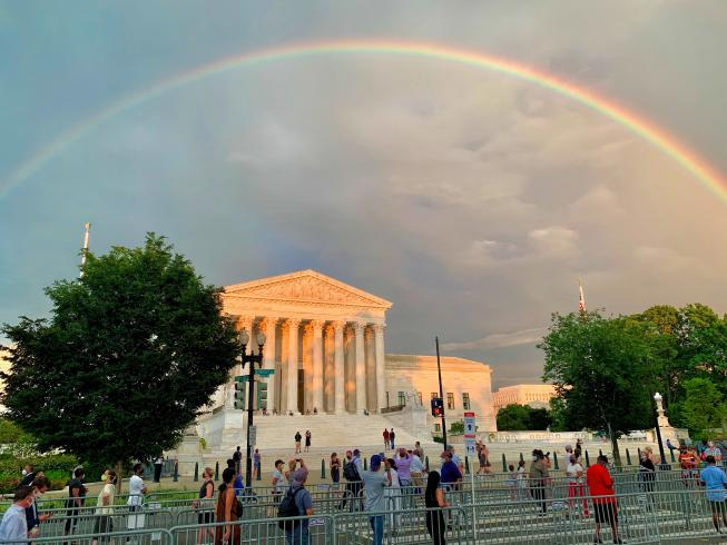 Photograph of people in socially distanced lines, waiting to pay respects to Representative John Lewis are treated to a rainbow over the Supreme Court.