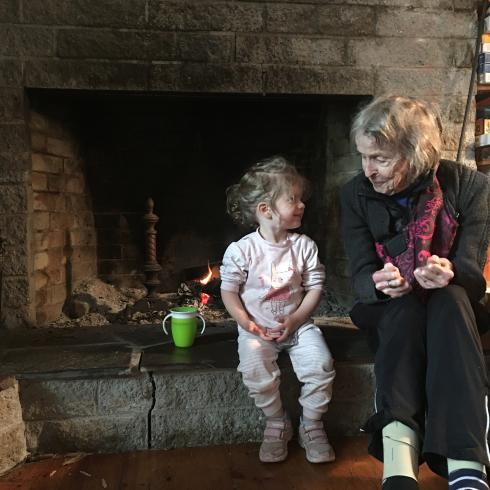 Photograph of a small child sitting with their grandmother next to a fireplace