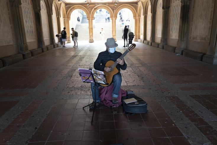 Photograph of person playing the guitar in an empty tunnel