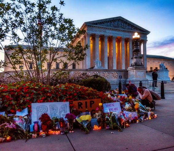 Photograph of flowers and candles in front of the Supreme Court