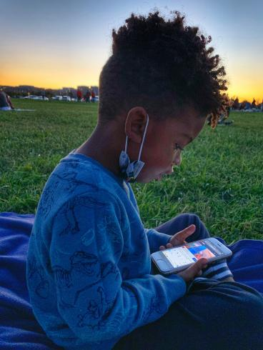 Photograph of a child looking at an iPhone, on a grassy field