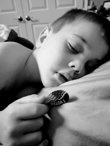 "Photograph of a young boy asleep, with an ""I Voted"" sticker in his hand"