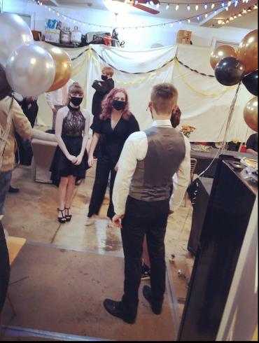 Photograph of a small group of high school students dressed up for a dance in a garage, with masks on, due to covid