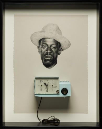 A blue clock sits underneath a portrait of a black man in a hat.