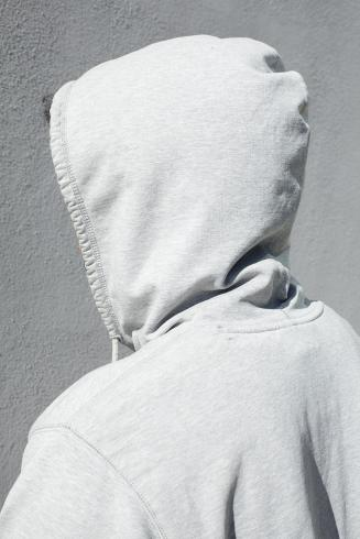 A person in a hoodie stands with their back to the viewer.