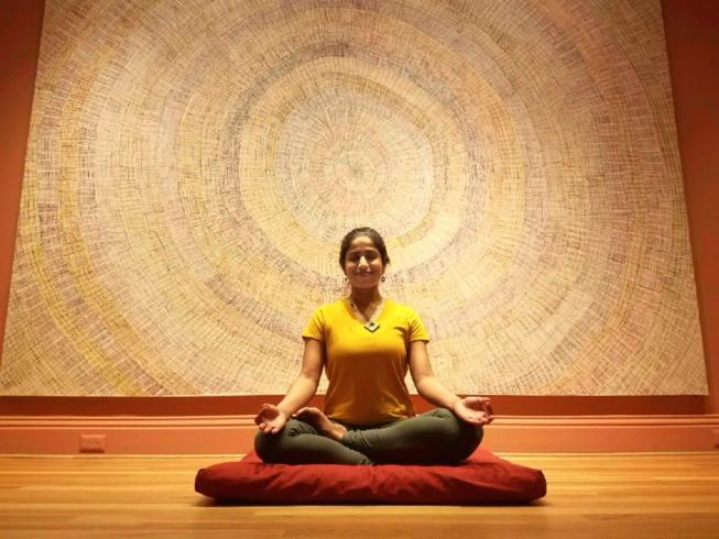 Aparna Sadananda meditating in the Marking the Infinite galleries