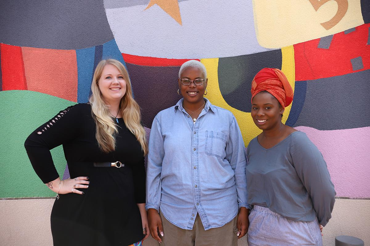 Photo of three woman smiling and posing in front of a colorful mural
